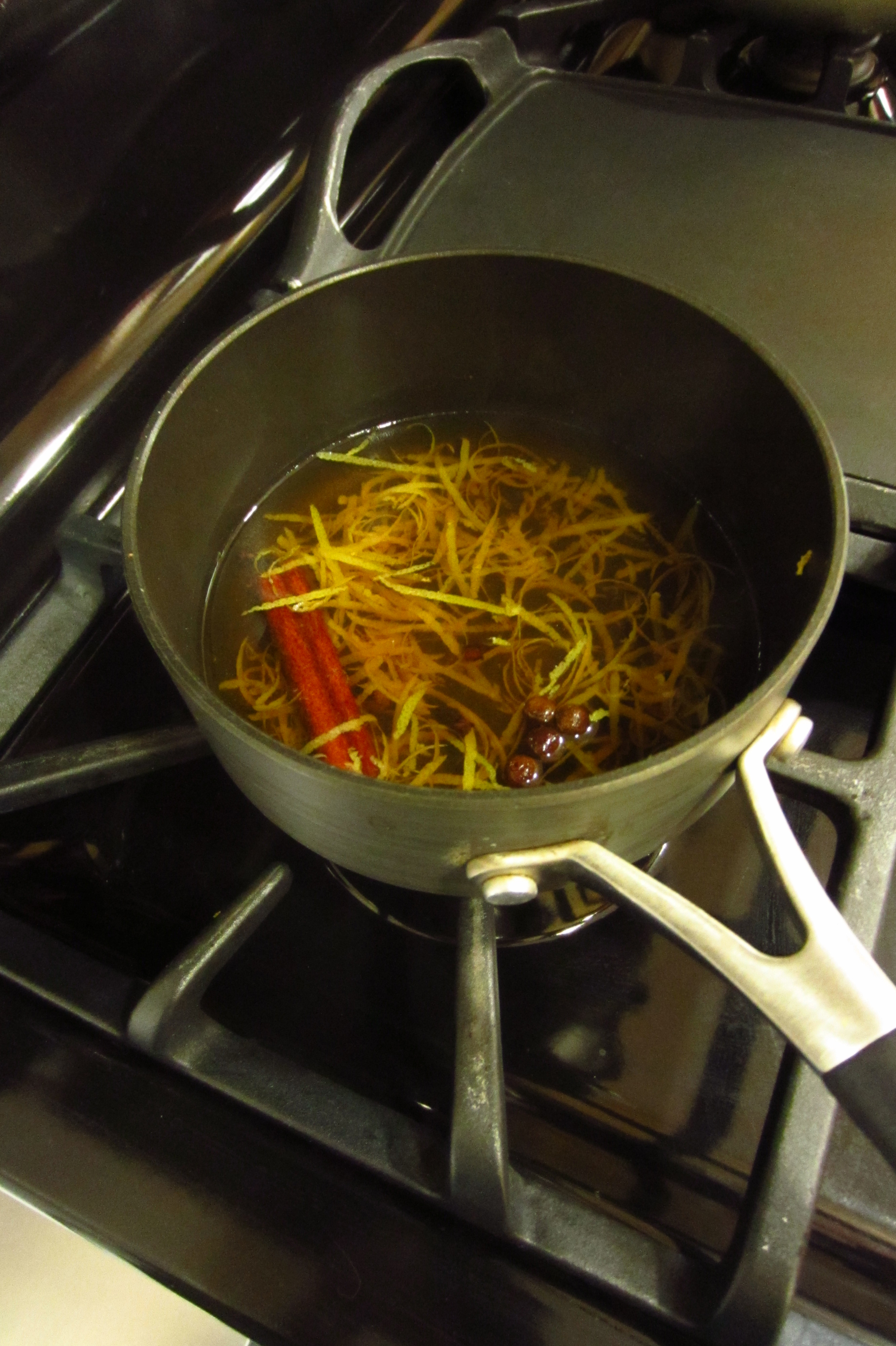 heating zest and spices in bourbon